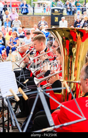 Salvation Army band performing on summer's day at the bandstand on Broadstairs seafront. Over shoulder view of five cornet players in red uniforms. - Stock Photo