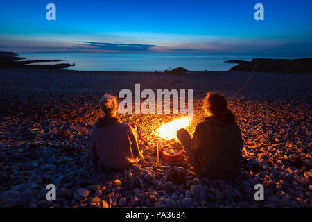 A couple of female friends sitting around a camp fire on a pebble beach at the popular coastal shore of Penmon Point on Anglesey watching the sunset - Stock Photo