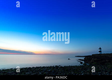 Last light and sunset at Penmon Point with the James Walker designed Trwyn Du Lighthouse on the shoreline as the sun sets across the Irish Sea - Stock Photo