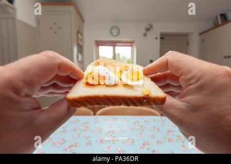 A point of view person holding a piece of bread with fresh made hard boiled egg with white and yoke on moving towards the persons mouth - Stock Photo