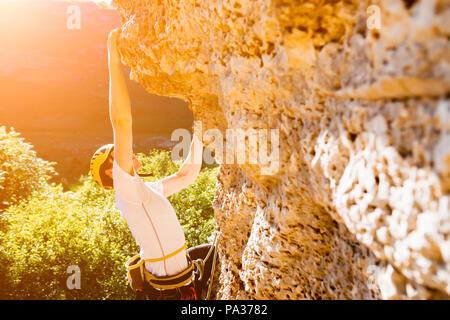 Photo of man in helmet climbing up on mountain - Stock Photo