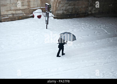 looking down onto an adult man walking across frame through the snow under grey umbrella towards a tunnel in Montpellier, France - Stock Photo