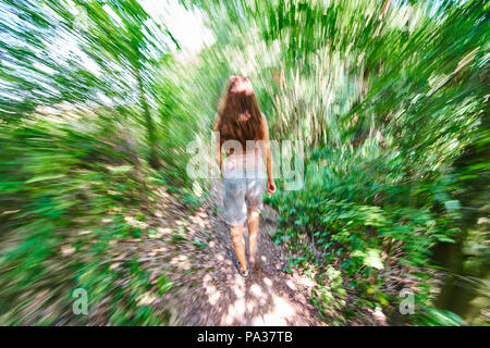 Woman running through a forest in Pfaffenhofen a.d.Ilm, Germany July 20, 2018 © Peter Schatz / Alamy Stock Photo - Stock Photo