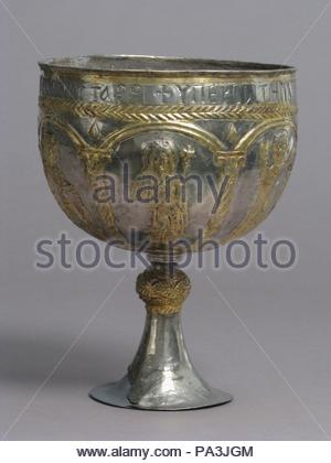 The Attarouthi Treasure - Chalice, 500–650, Made in Attarouthi, Syria, Byzantine, Silver and gilded silver, Overall: 8 3/8 x 6 5/16 in. (21.3 x 16 cm), Metalwork-Silver, With a long-haired Saint John the Forerunner, the Virgin Mary in orant pose, a saint in orant pose, a military saint with staff and shield, a youthful Christ with cruciform halo, and another military saint in armor killing a dragon (Saint George ?), under arcades. Inscribed in Greek: For her salvation Eudoxia has offered [this] to Saint Stephen of the village of Attar[outhi]. - Stock Photo