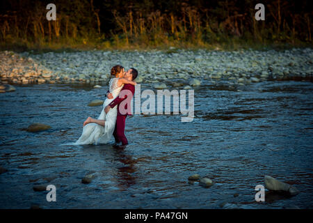 Horizontal wedding shot of the beautiful newlyweds. The groom in red suit is kissing and lifting up his charming bride while standing in the middle of the river during the sunset. - Stock Photo