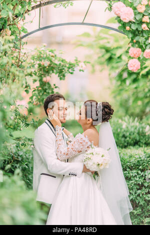 Sensitive outdoor portrait of the bride touching the face of the groom under the rose arch in the garden. - Stock Photo