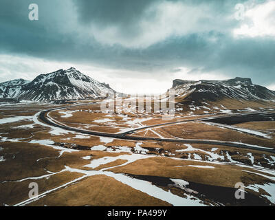 Iceland aerial view Landscape with snow and clouds, street and yellow and green grass - Stock Photo
