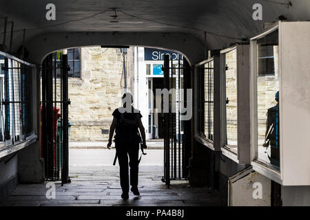 The silhouette of a person figure walking through a covered walkway in Truro City centre in Cornwall. - Stock Photo