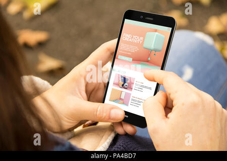 mobile design concept: woman holding a 3d generated smartphone with tutorial design on the screen. Graphics on screen are made up. - Stock Photo