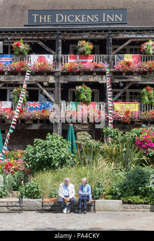 an elderly couple sitting outside of the dickens in public house at st Katherine docks in central London. floral display at public house in london - Stock Photo
