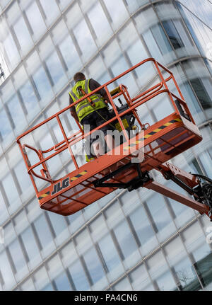 a man using a mobile elevated work platform or MEWP cherry picker  to gain access to a tall glazed office block in central london - Stock Photo