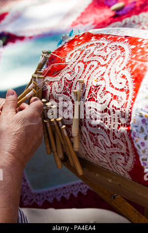 SANTA MARGHERITA LIGURE, ITALY - APRIL 29, 2017: Unidentified woman doing pillow lace making on street of Santa Margherita Ligure in Italy. In this pa - Stock Photo