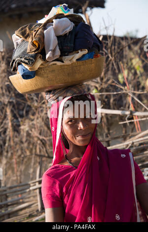 Indian woman carrying her clothes basket on her head in Kanha village near the Kanha National Park, in India - Stock Photo