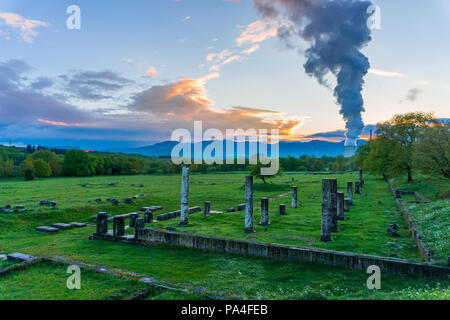 Ancient theater of Megalopolis (4th century BC), the largest in Greece with a 20000 spectator capacity. Lignite fired power plants in the background - Stock Photo