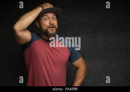 Portrait of Black bearded male in cap over grey background. - Stock Photo