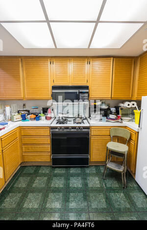 Messy condo kitchen vertical view with oak cabinets, tile countertops, gas stove, green flooring and piles of dishes. - Stock Photo