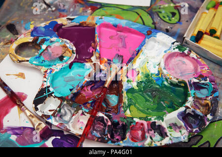 Beautiful colorful textured background, paint strokes on paper and left overs residues of paints in palette colour array on table, spots and blotches  - Stock Photo