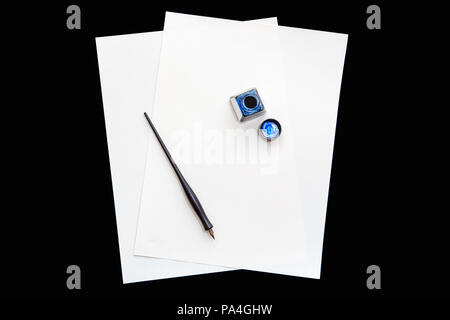 Two isolated white blank sheets of paper on black background, with pen and open bottle of blue ink, education concept, copy space for text - Stock Photo