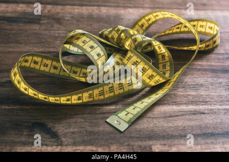 A Loose Messed Up Yellow Measuring Tape On An Old Wooden Table - Stock Photo