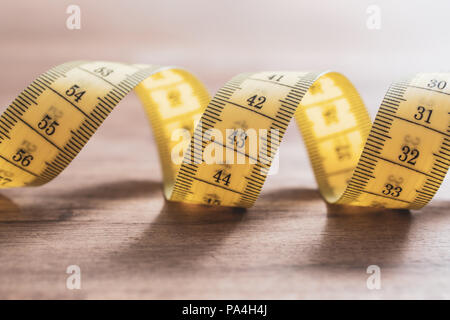 Soft Yellow Measuring Tape in Spiral Shape On A Table - Stock Photo