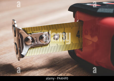 Macro Of A Solid Measuring Tape With Pulled Out Scale Lying On A Table - Stock Photo