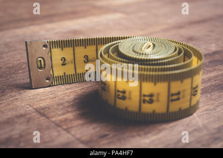 Macro Of A Rolled Up Yellow Measuring Tape On A Wooden Table - Stock Photo