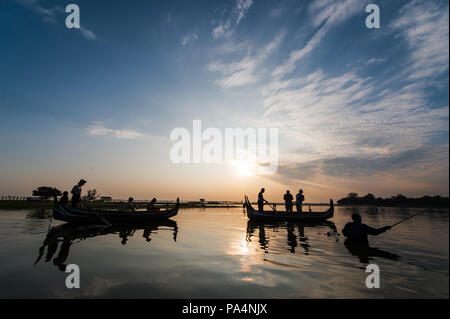 Boats with tourists on the Taung Tha Man Lake with the U Bein Bridge in the background during a sunset in Mandalay, Myanmar - Stock Photo