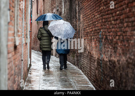 Women walk on a narrow alleyway (street) and hide under umbrella during a rainy day in Venice, Italy - Stock Photo