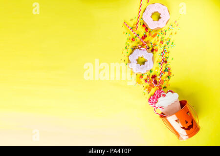 Halloween sweets concept, bucket in the form of a festive pumpkin, full of sweets and candies, cookies, jellies, desserts, bright yellow background to - Stock Photo