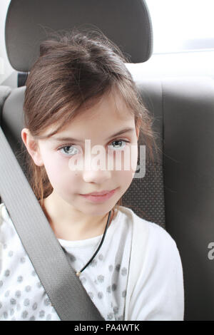 Portrait of cute elementary age young girl sitting in car wearing a seat belt. Child transportation safety concept. - Stock Photo