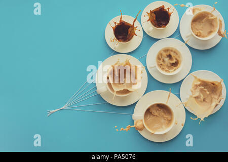 Hand holding coffee cups with milk and without in shape of balloons on blue paper background. Toned. Weather or good morning concept. - Stock Photo