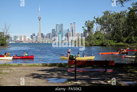 children in canoes on Toronto Islands with the Toronto city skyline in the background, Canada - Stock Photo
