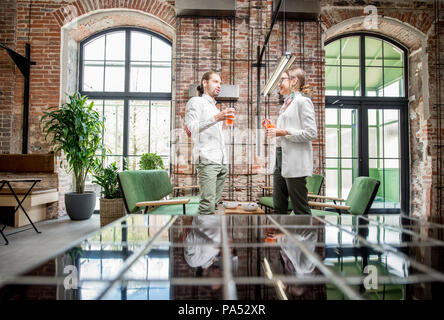Young couple dressed in white standing together with drinks during the conversation in the beautiful spacious loft interior - Stock Photo