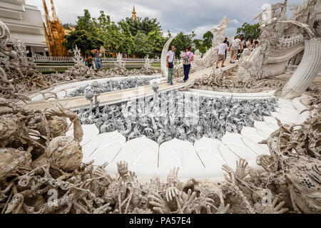 Chiang Rai (Thailand) - 10 June 2017: People are visiting the Wat Rong Khun, better known as the White Temple, a contemporary and unconventional Buddh - Stock Photo