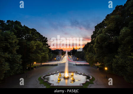 Fountain at Friedensengel, where is the famous landmark with light trail of car of transportation on avenue for sunset time in Munich, Germany, Europe - Stock Photo