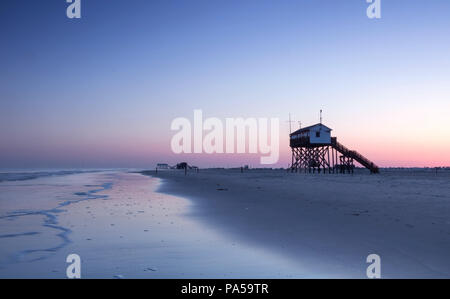 Stilt house at the beach of St. Peter-Ording at sunrise - Stock Photo