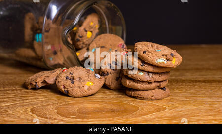 Choc chip smartie cookies falling out of jar on wooden table top. - Stock Photo