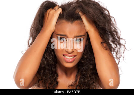 young dark skinned girl has itching in her hair - Stock Photo