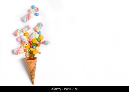 Ice cream cone flat lay image with colorful candy packing into the cone. - Stock Photo