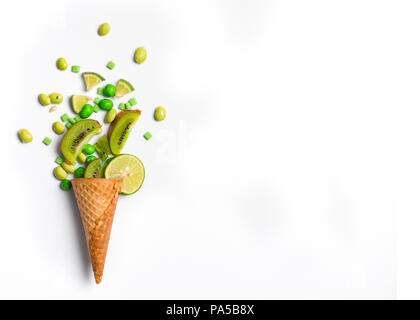 Ice cream cone flat lay image with green candy and kiwifruit packing into the cone. - Stock Photo
