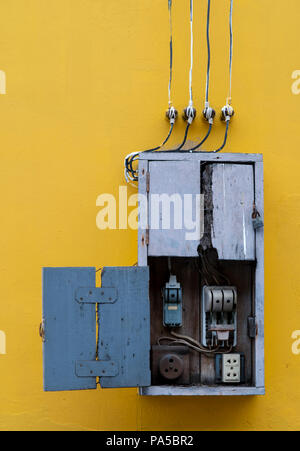 Wooden box, electric control equipment in the factory on yellow vintage concrete wall background. Manual cut out with old design. Safety in home and f - Stock Photo