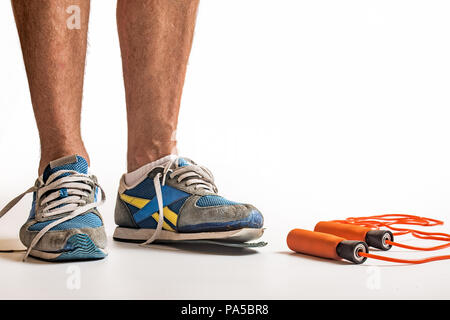 man standing wearing worn out pair of trainers, white background with copy space. - Stock Photo