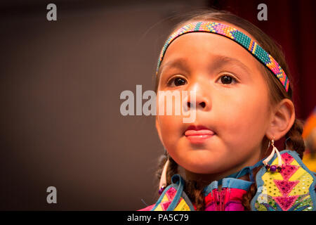 Close up portrait of little Native American girl dressed in colorful headband, ear rings and dress looking ahead with tongue between lips. - Stock Photo