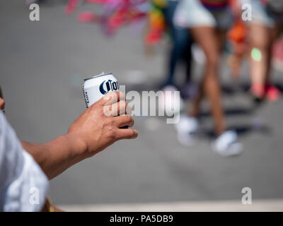 Man s hand drinking canned Corona can in a festive urban setting - Stock Photo