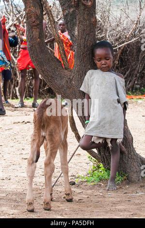 AMBOSELI, KENYA - OCTOBER 10, 2009: Portait of an unidentified Massai little boy and his goat near a tree in Kenya, Oct 10, 2009. Massai people are a  - Stock Photo