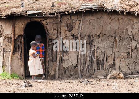 AMBOSELI, KENYA - OCTOBER 10, 2009: Unidentified Massai boy and girl near theit house in Kenya, Oct 10, 2009. Massai people are a Nilotic ethnic group - Stock Photo