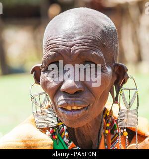 AMBOSELI, KENYA - OCTOBER 10, 2009: Portrait of an unidentified Massai extraordinary woman with heavy earings in Kenya, Oct 10, 2009. Massai people ar - Stock Photo