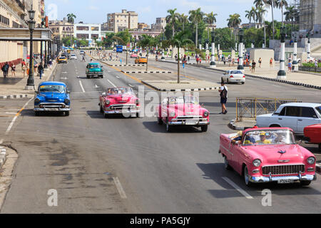American classic cars, vintage taxies carrying tourists and visitors on Paseo de Marti in Havana, Cuba - Stock Photo