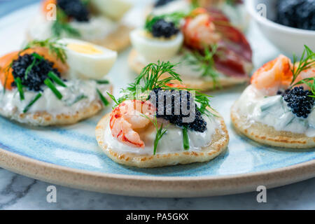 Selection of cocktail blinis with salmon, cured bresaola, crayfish, caviar, quail eggs and sour cream - gourmet party food - Stock Photo
