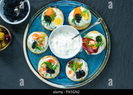 Selection of cocktail blinis with salmon, cured bresaola, crayfish, caviar, quail eggs and sour cream - gourmet party food - top view - Stock Photo